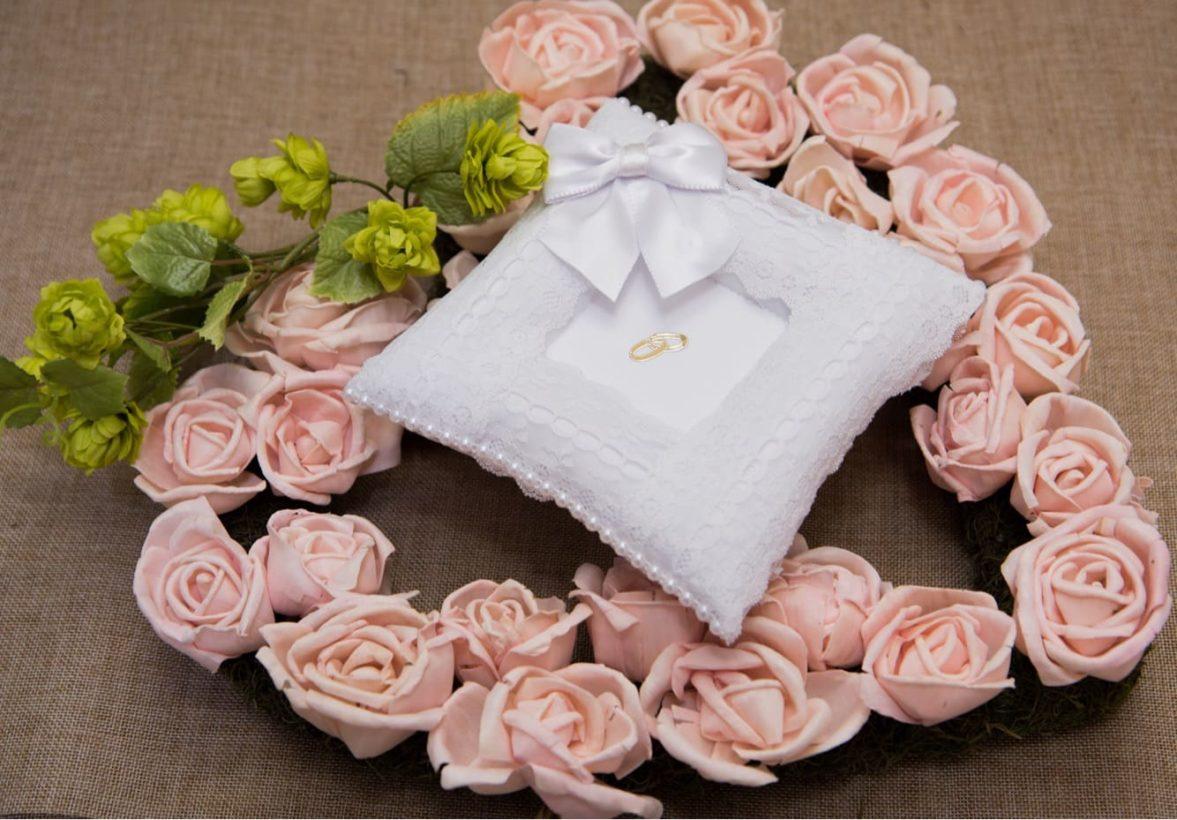 Белоснежная подушечка для колец, деликатно украшенная по краям кружевной тканью.