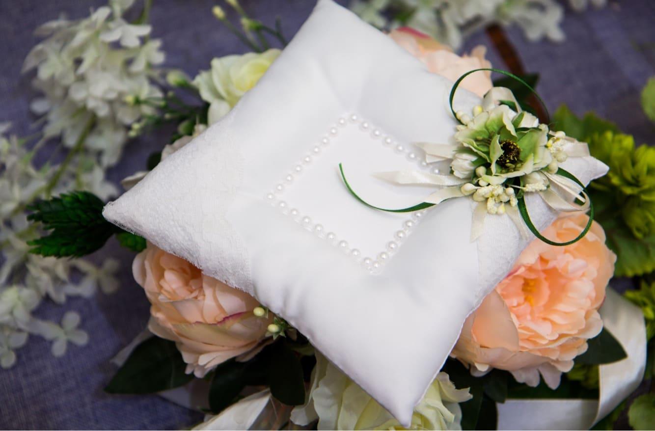 Изысканная белоснежная подушечка для колец, в центре декорированная жемчугом.
