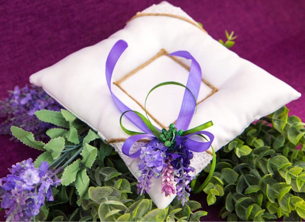 Изящная белая подушечка для колец, украшенная фиолетовыми бутонами и лентой.