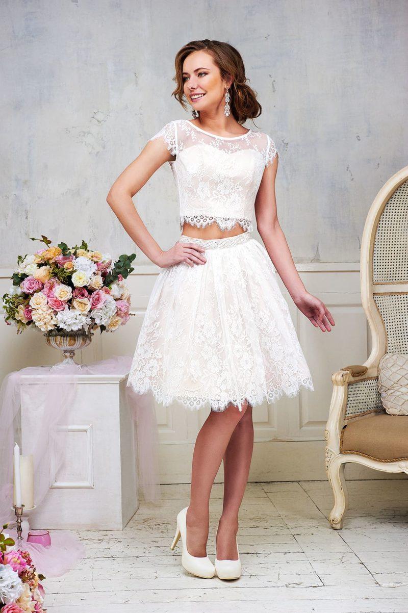 Кружевное свадебное платье с юбкой длиной до колена и кокетливым укороченным топом.