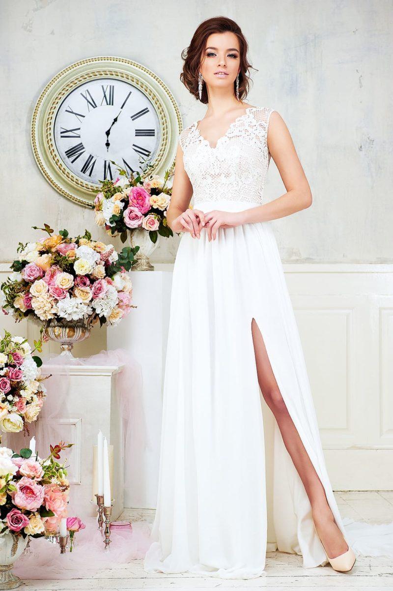 Прямое свадебное платье с разрезом на юбке и кружевным верхом с V-образным лифом.