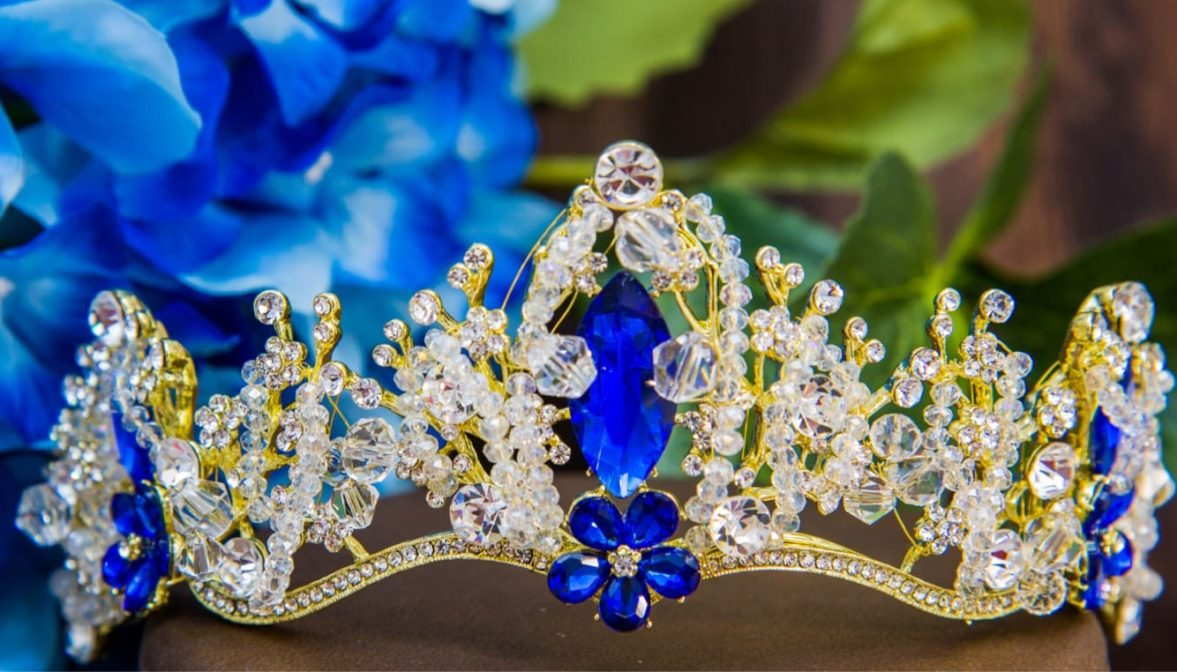Чарующая свадебная корона из золотистого металла с прозрачными и голубыми кристаллами.
