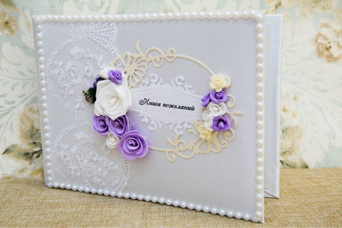 Белоснежная свадебная книга для пожеланий, украшенная фиолетовыми цветами.