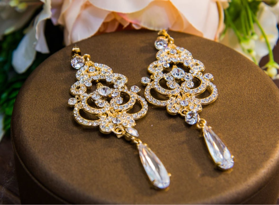 Золотистые сережки с длинными подвесками, украшенные стразами по всей длине.