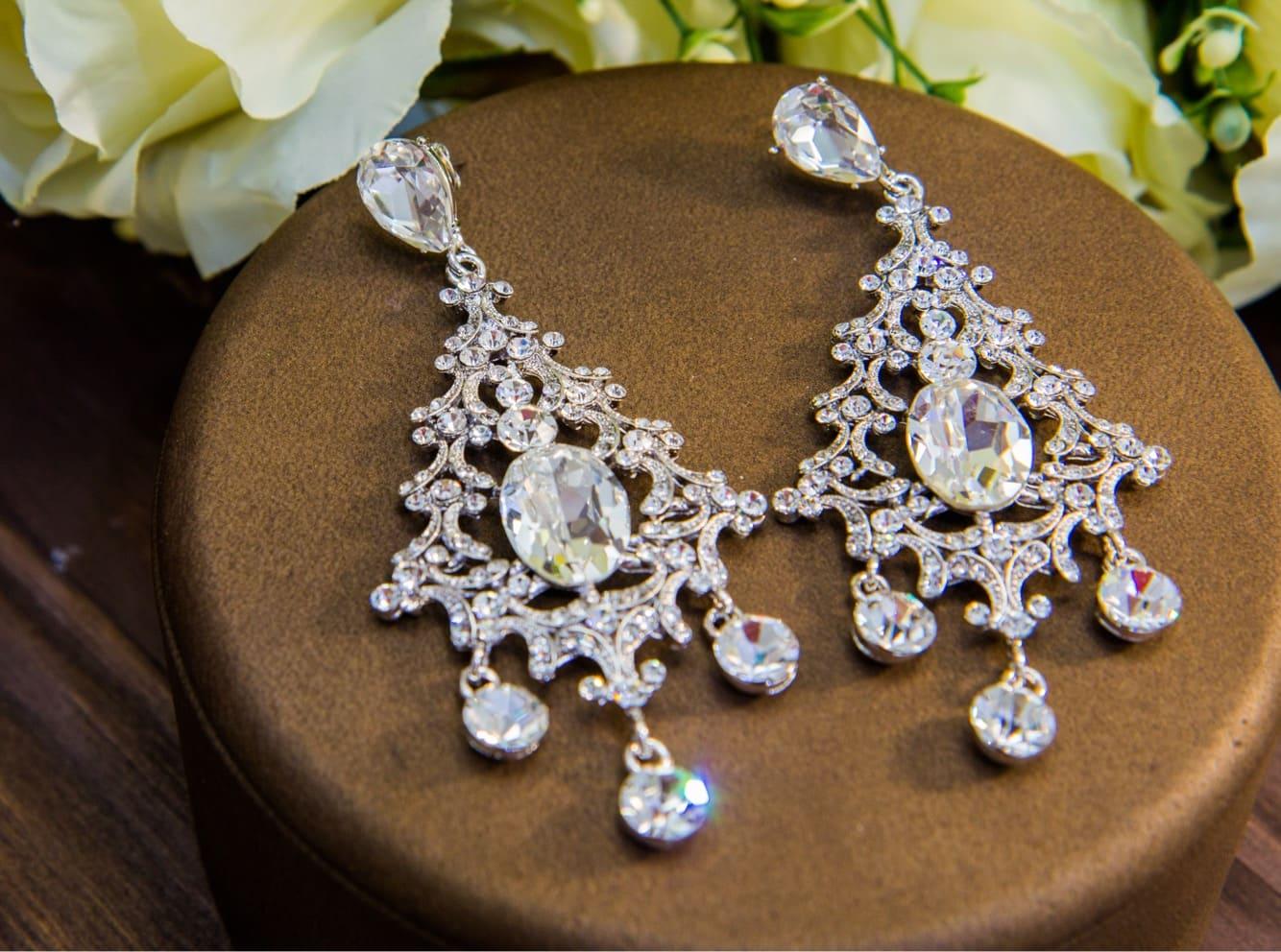 Изысканные сережки с фигурными подвесками и крупными серебристыми кристаллами.