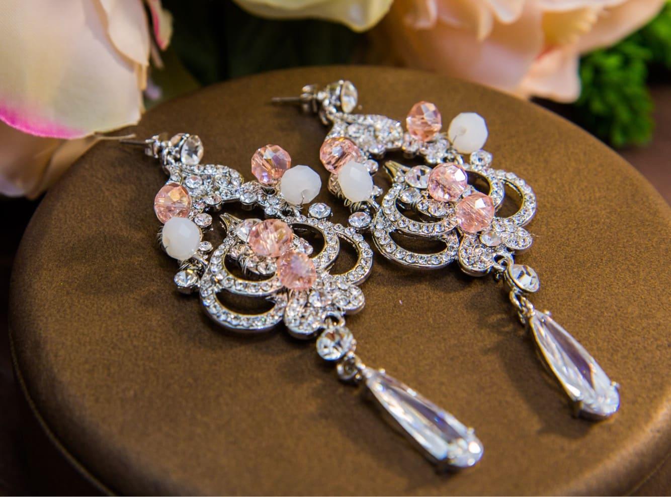 Романтичные серьги с подвесками, украшенные прозрачными и розовыми кристаллами.