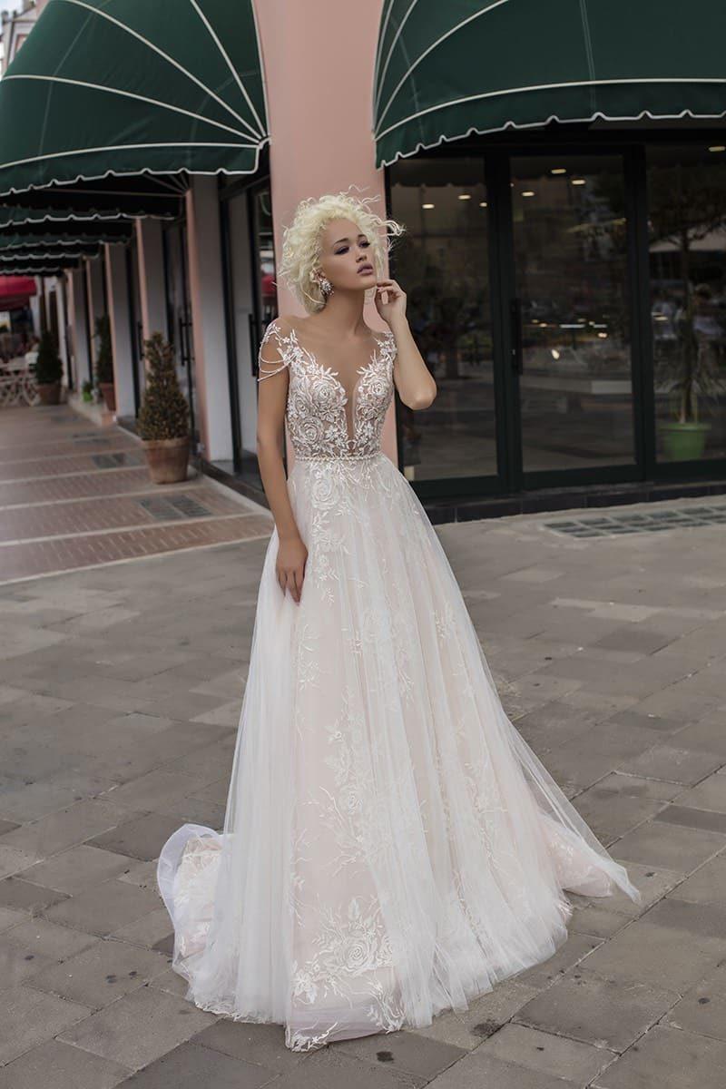 Свадебное платье «принцесса» с глубоким вырезом лифа и романтичным кружевным декором.