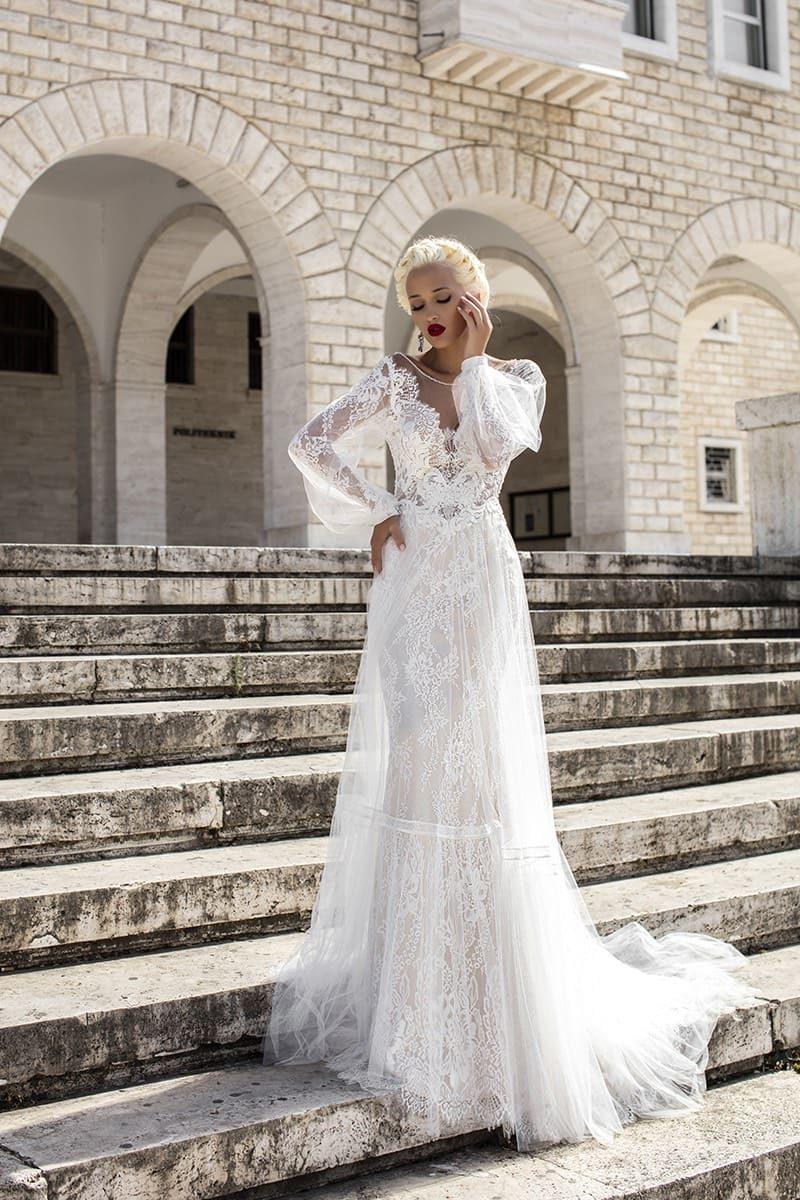 Свадебное платье с воздушной верхней юбкой и длинными кружевными рукавами.
