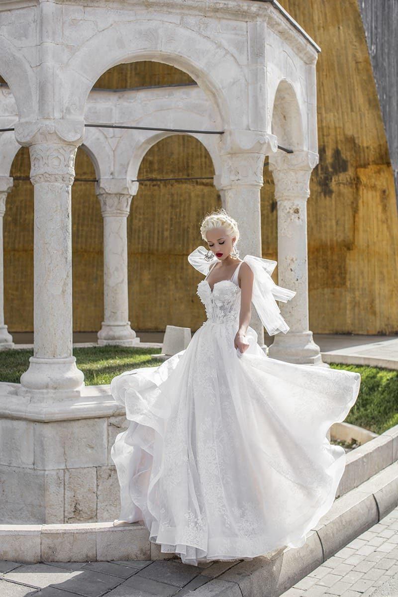 Необычное свадебное платье с юбкой А-силуэта и пышными бантами на бретельках.