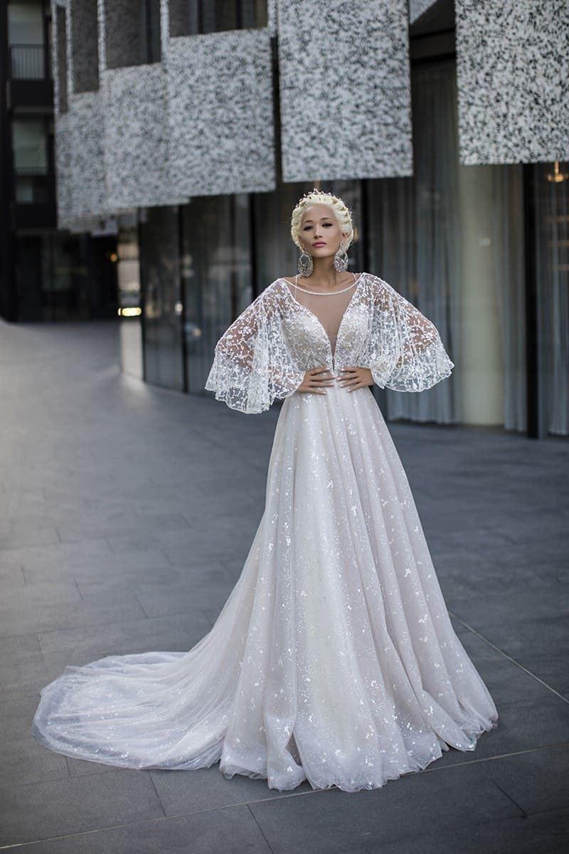 Свадебное платье А-силуэта с роскошным широким рукавом и длинным шлейфом сзади.