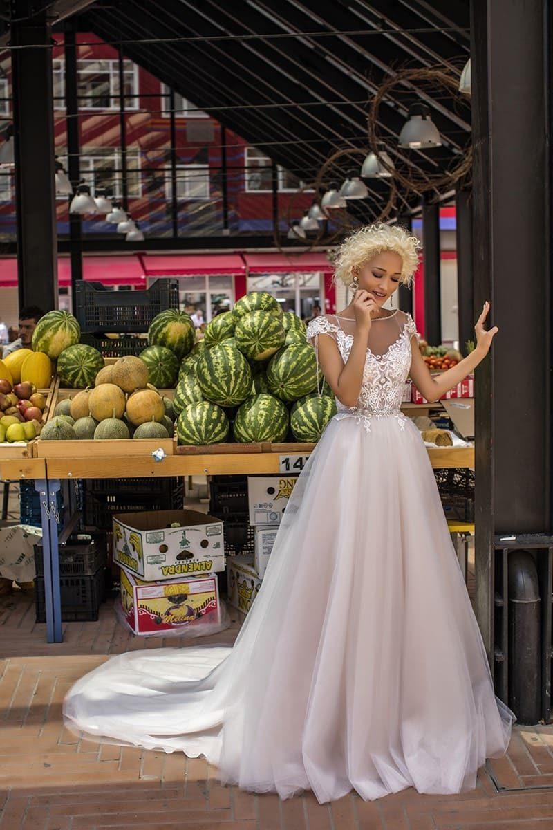 Свадебное платье цвета слоновой кости с кружевным верхом и воздушной юбкой со шлейфом.