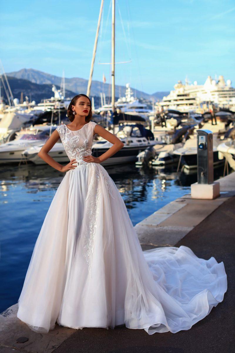 Пышное свадебное платье розового оттенка с закрытым лифом и длинным шлейфом.