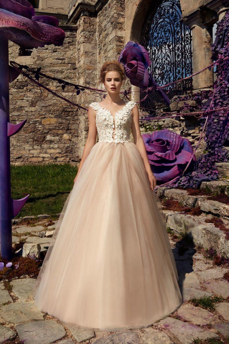 Свадебное платье с многослойной кремовой юбкой и лифом с белым кружевом.