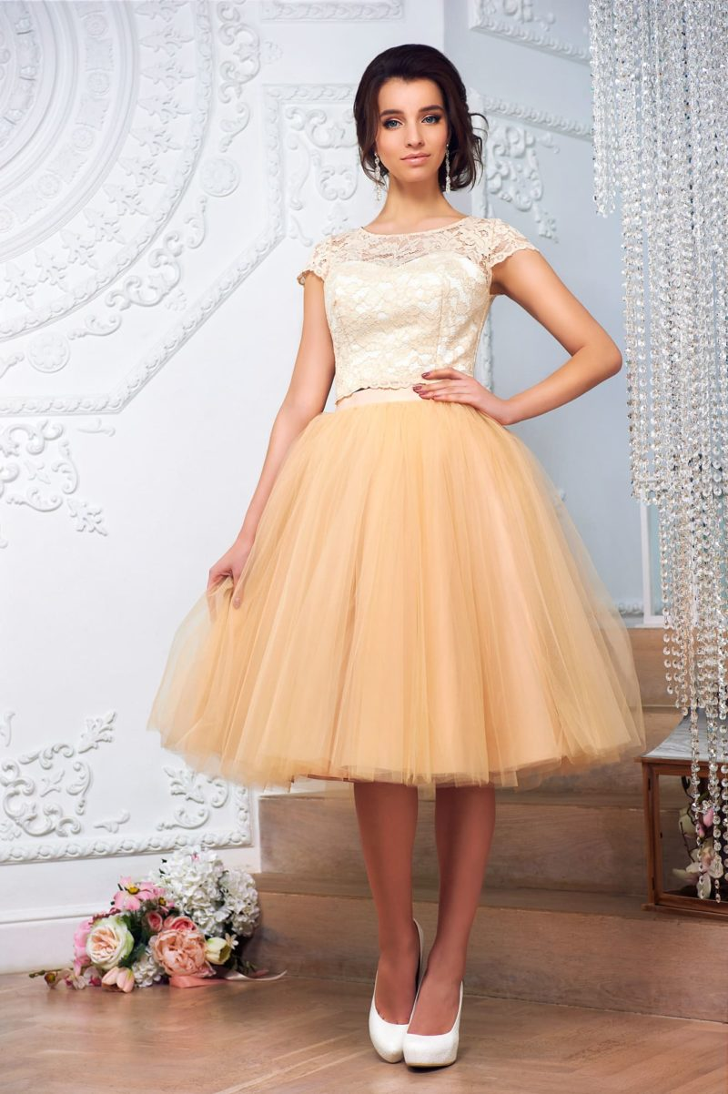 Золотистое свадебное платье с пышной юбкой до колена и закрытым верхом с кружевом.