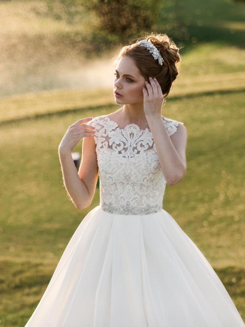 Классическое свадебное платье с закрытым кружевным лифом и блестящим декором пояса.