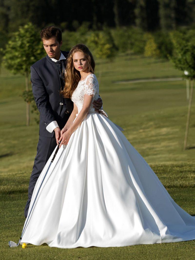 Пышное свадебное платье с атласной юбкой А-силуэта и закрытым кружевным верхом.