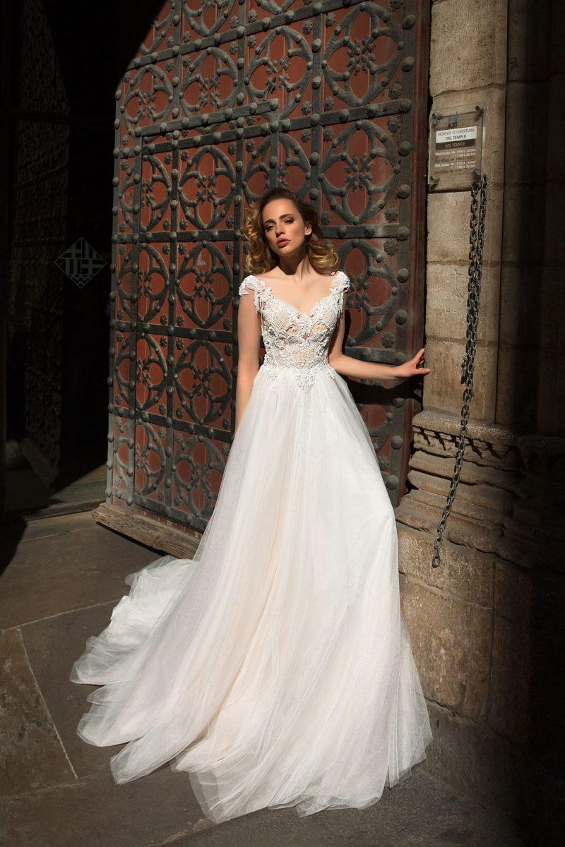 Свадебное платье женственного А-силуэта с прозрачной спинкой и бежевым лифом.