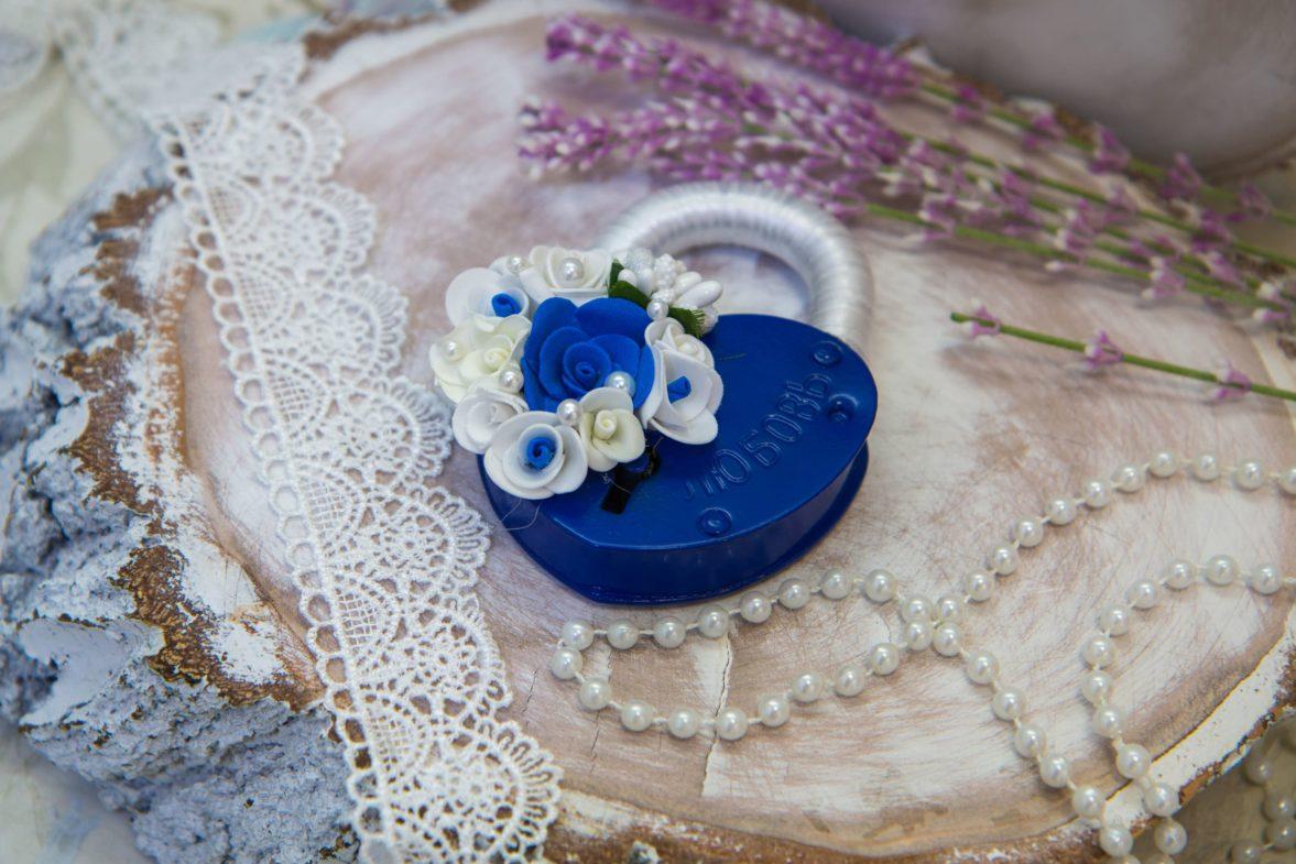 Синий свадебный замок с отделкой белой лентой и объемными цветочными бутонами.