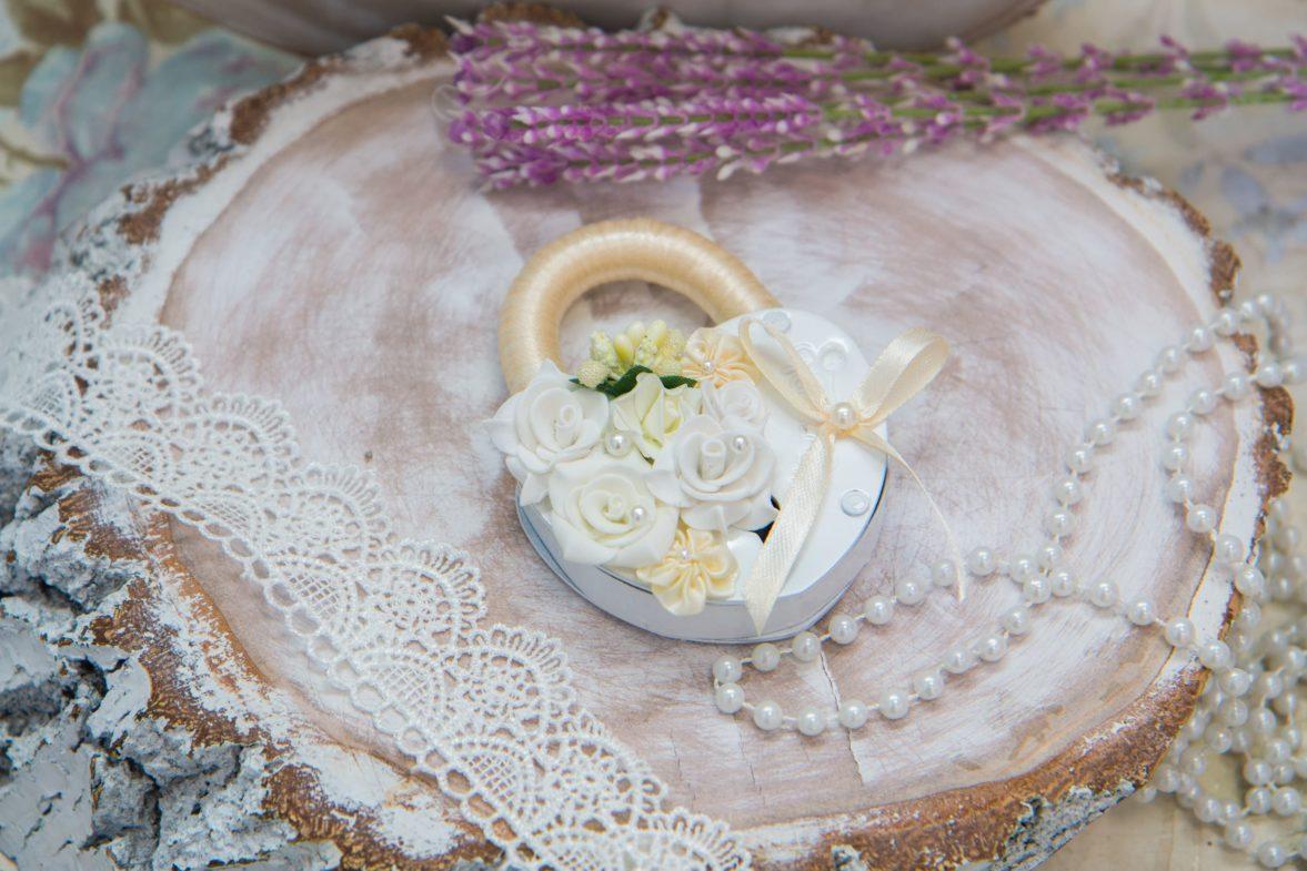 Свадебный замок белого цвета, украшенный цветочными бутонами и лентой.