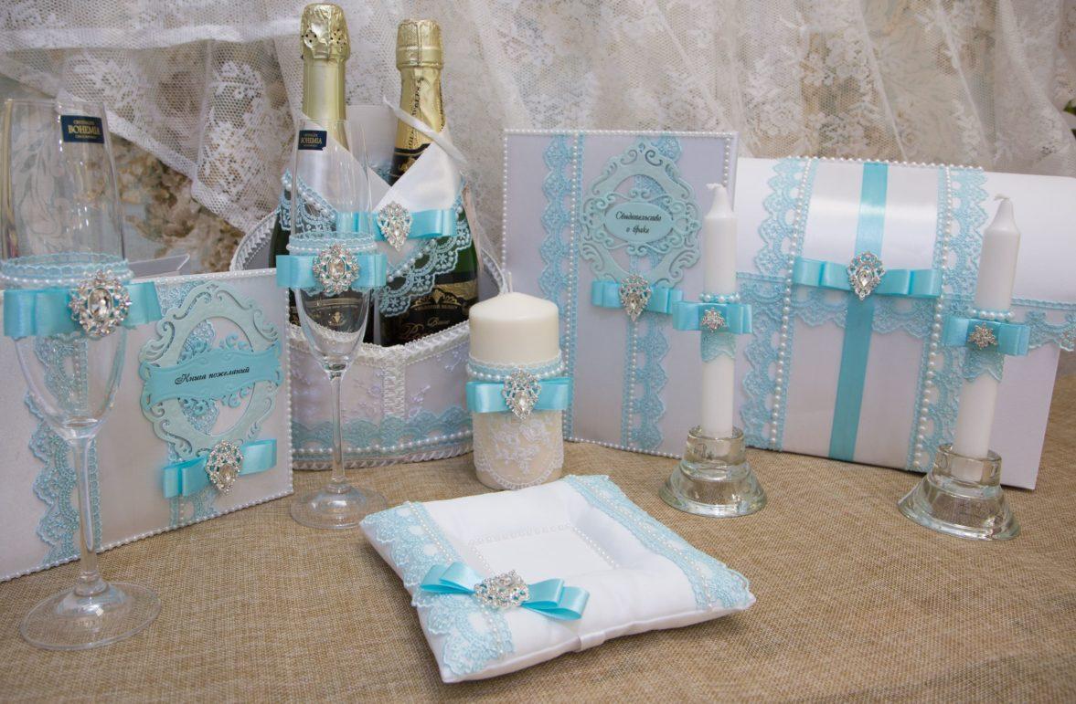 Свадебный набор из белого кружева, декорированный голубыми атласными лентами.