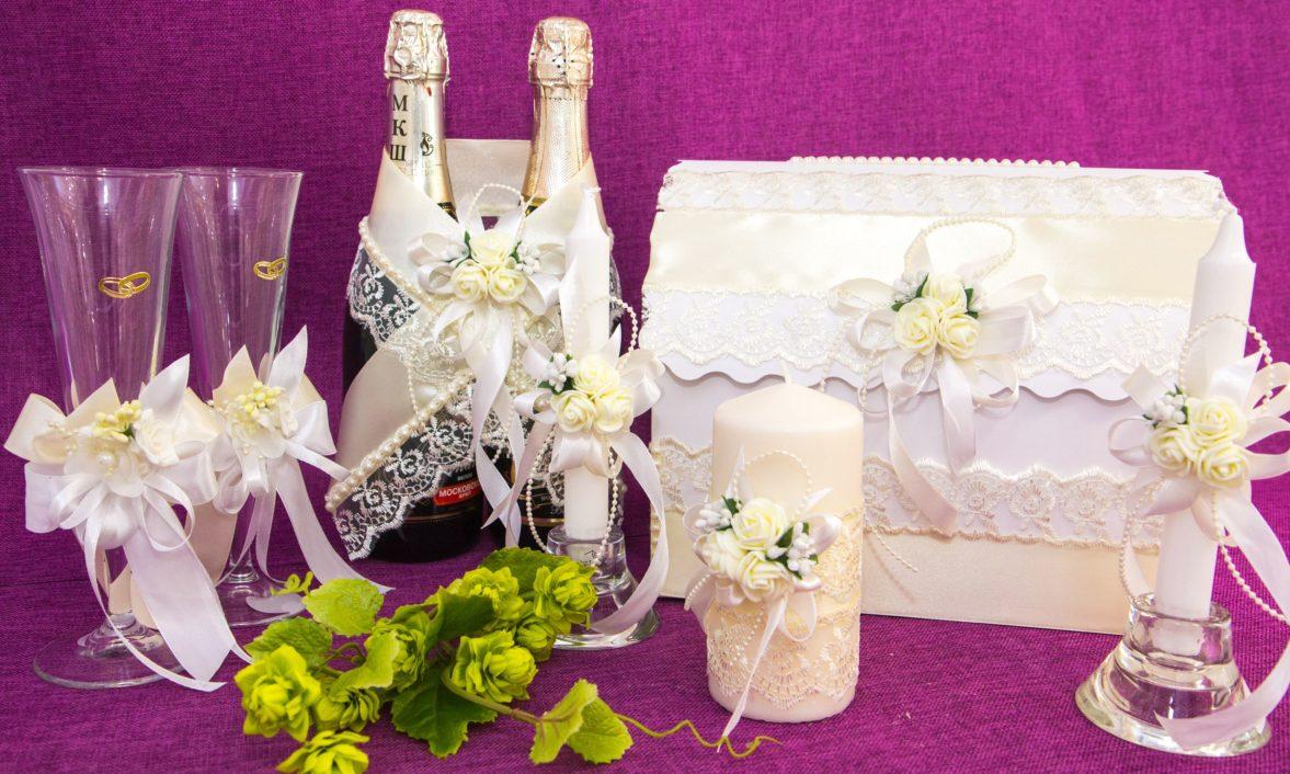 Свадебный набор из кружева, дополненного белыми лентами и кремовыми бутонами.