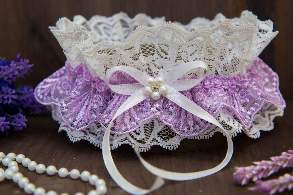 Кружевная подвязка в бело-лиловых тонах, украшенная бусинами и лентой.