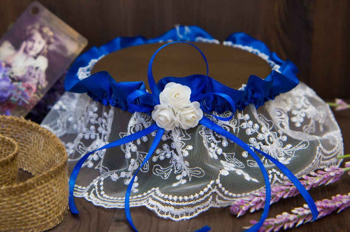 Белая кружевная подвязка, украшенная синей лентой и небольшими белыми бутонами.