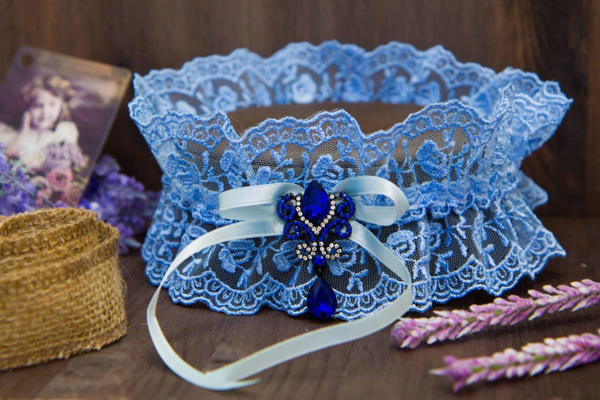 Голубая кружевная подвязка с декором из синих стразов и голубой ленты.