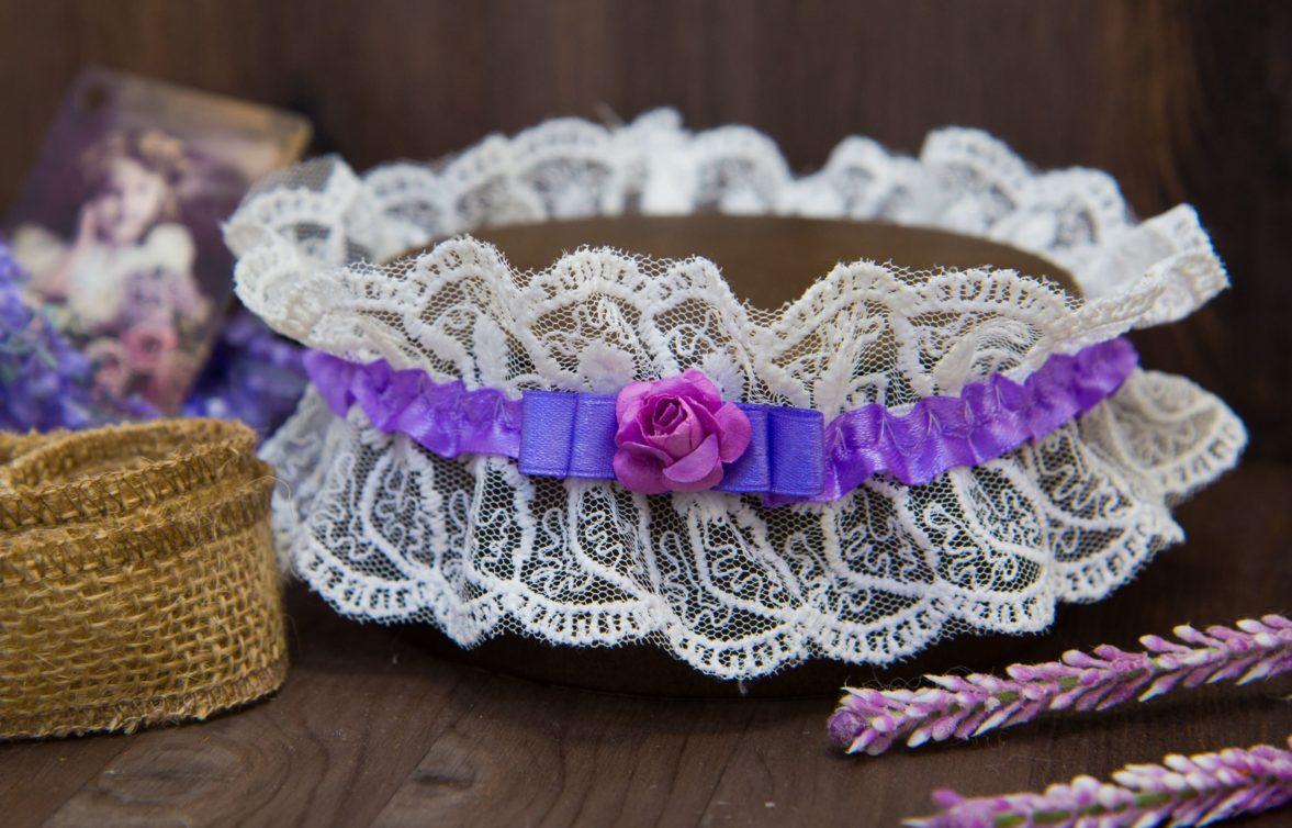 Романтичная подвязка из плотного кружева с лиловой лентой и маленькими бутонами.