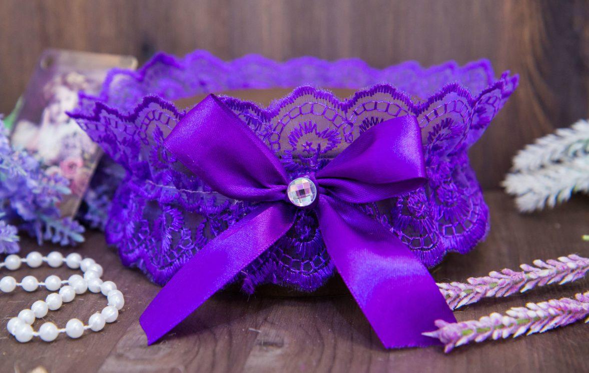 Фиолетовая кружевная подвязка, декорированная романтичным бантом со стразом.
