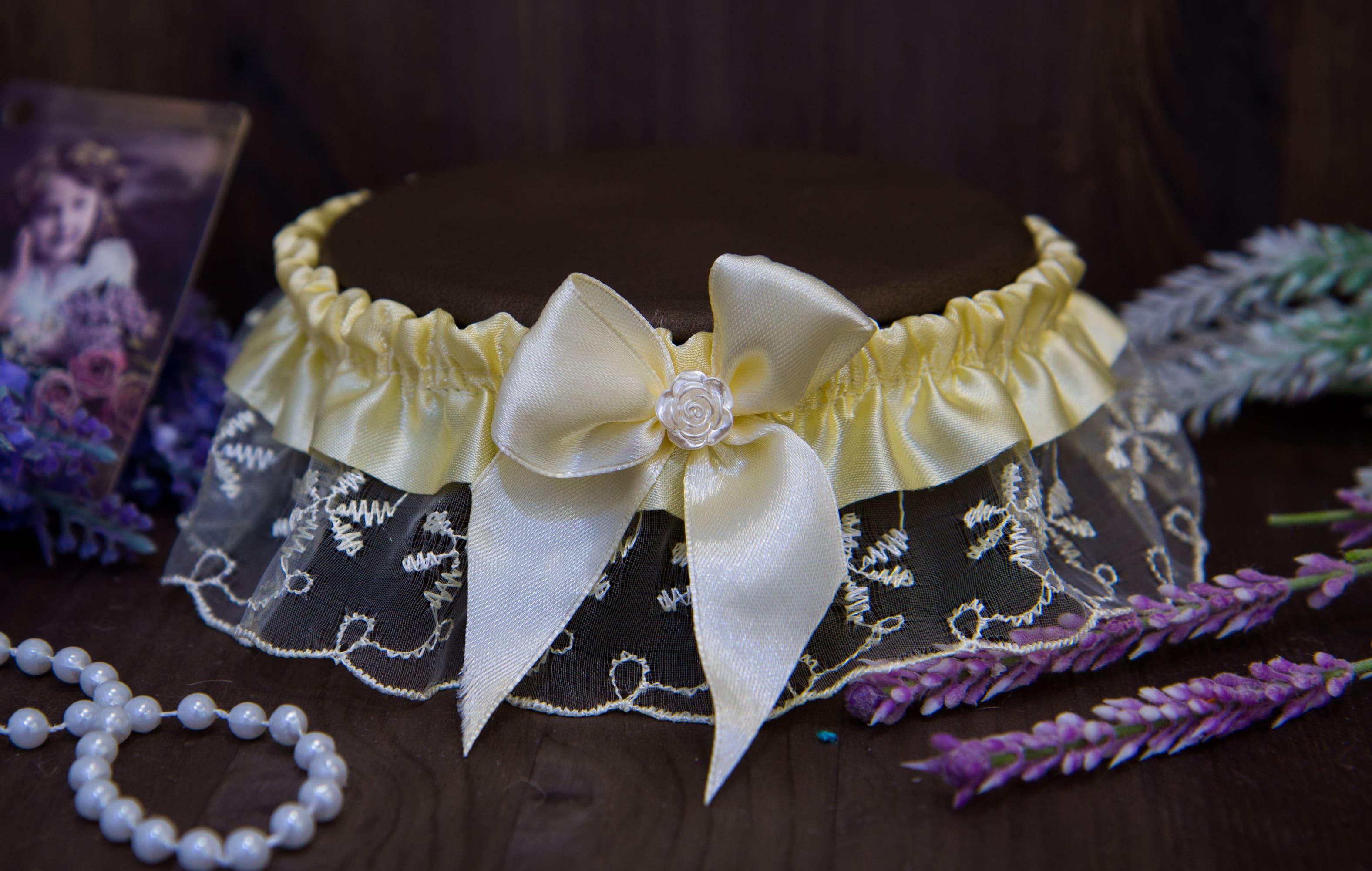 Прозрачная кружевная подвязка, декорированная кремовой лентой и бантом.