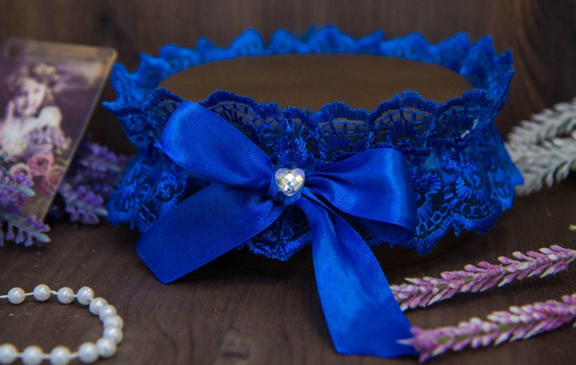 Синяя кружевная подвязка, декорированная бантом и стразом в форме сердечка.