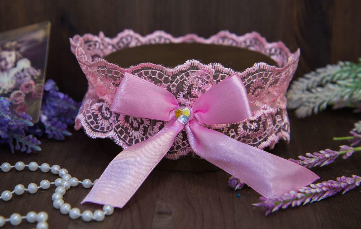 Романтичная кружевная подвязка розового цвета, украшенная объемным бантом.
