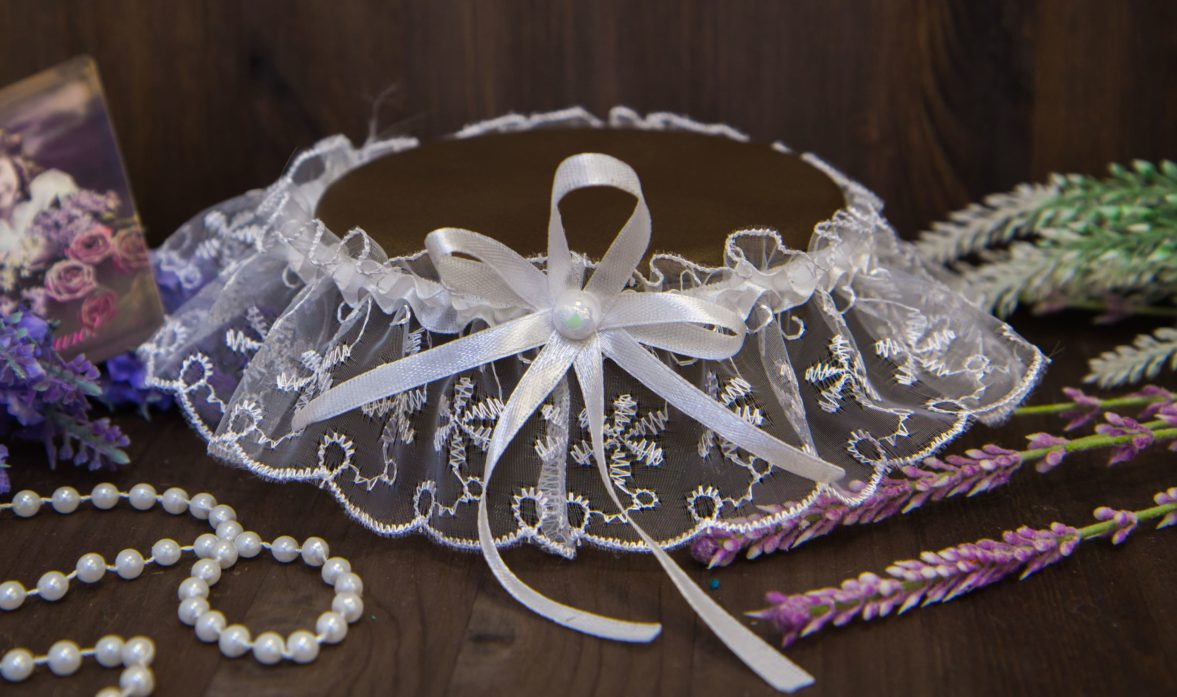 Деликатная кружевная повязка, декорированная спереди бантом и бусиной.