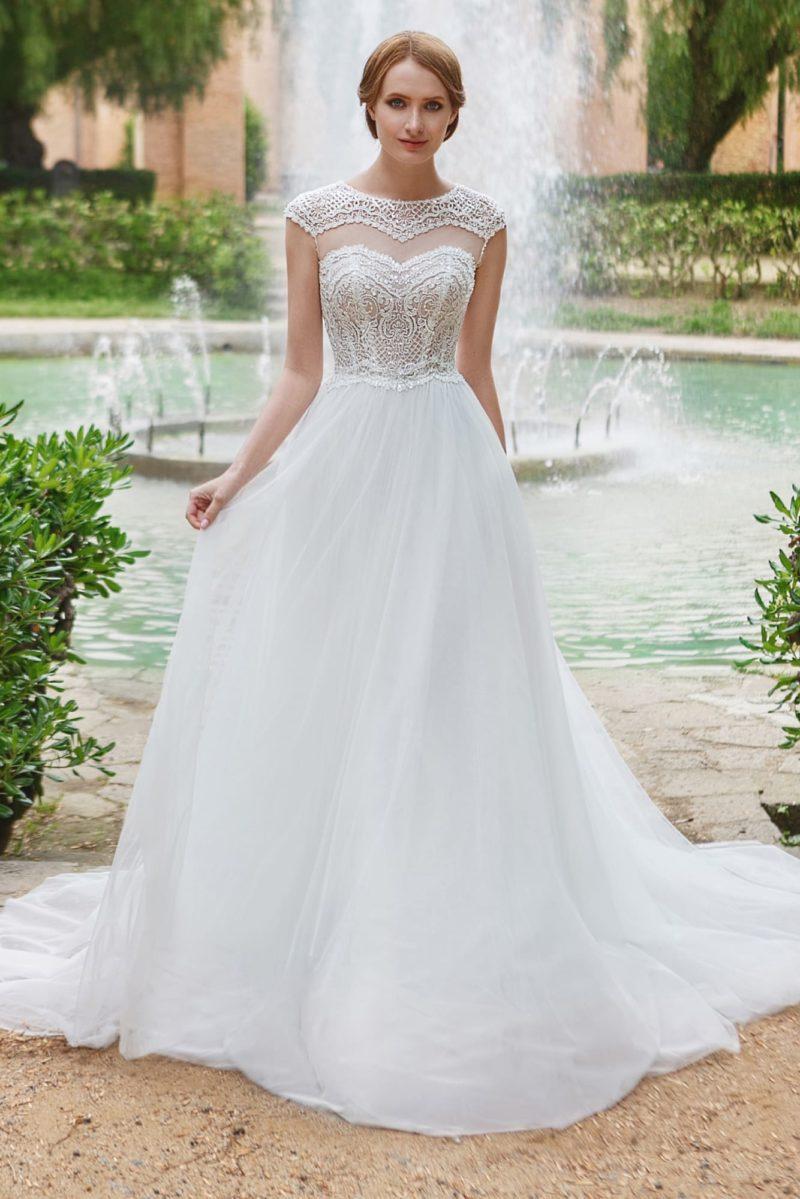 Свадебное платье с кружевными вставками над лифом и юбкой А-силуэта.