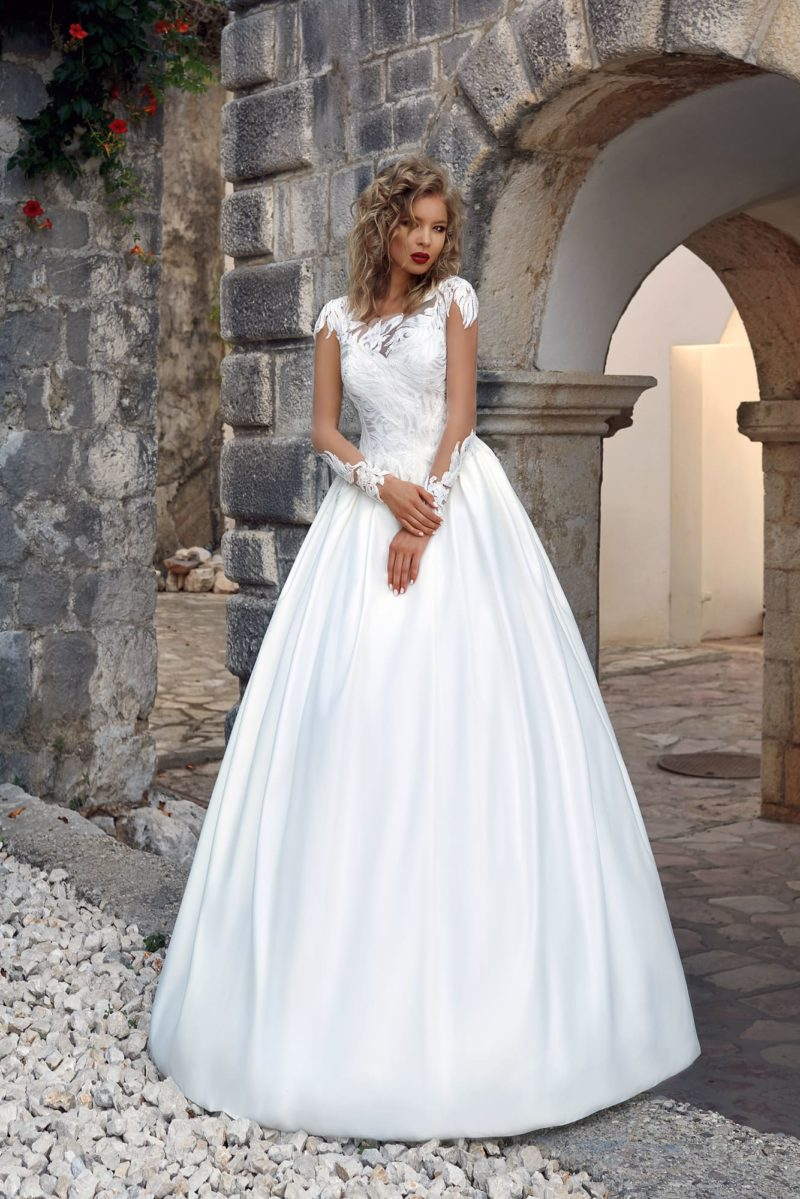 Свадебное платье с атласной юбкой и эффектным кружевом по закрытому верху.