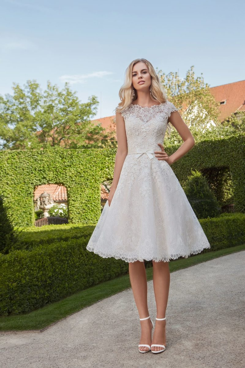 Свадебное платье длиной до колена с кружевным верхом и юбкой А-силуэта.