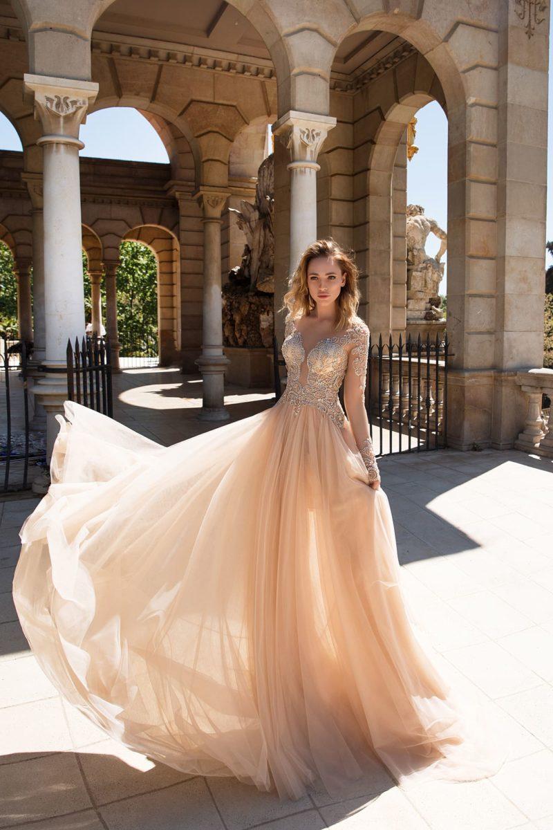 Вечернее платье бежевого цвета, с легкой шифоновой юбкой и длинным рукавом.