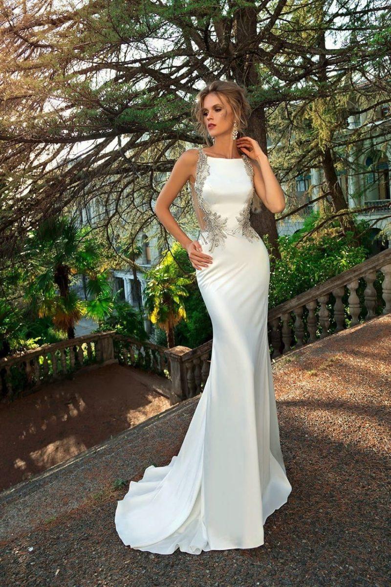 Облегающее свадебное платье с прозрачными вставками и притягательной спинкой.