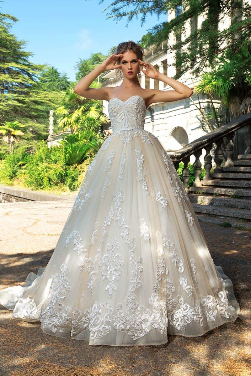 Свадебное платье пышного кроя с кремовой юбкой, открытым лифом и аппликациями.