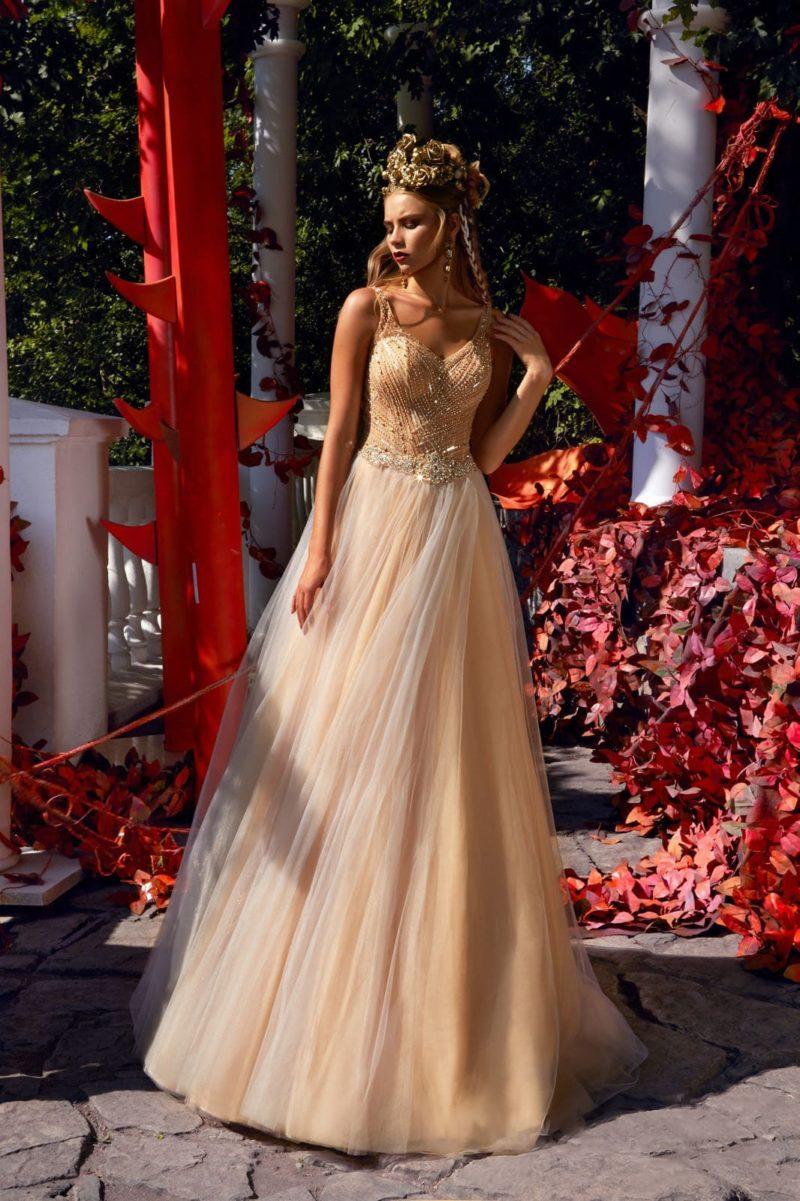 Золотистое свадебное платье А-силуэта с бисерной отделкой корсета и верхней юбкой.