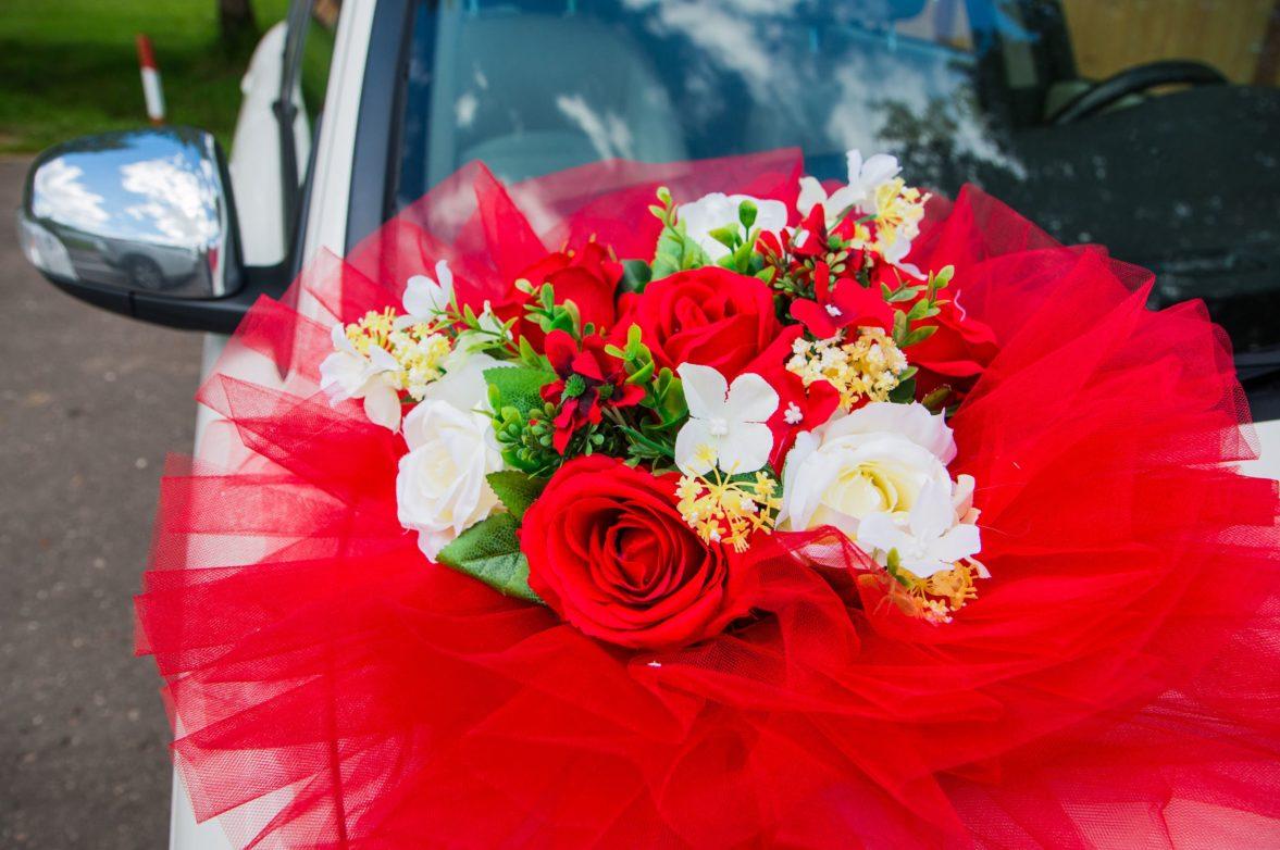 Украшение на машину с крупными цветочными бутонами и красной оборкой.