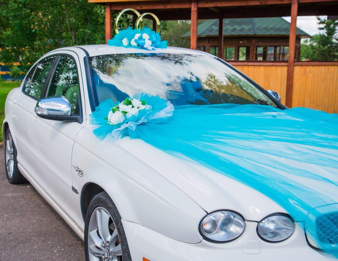 Голубое украшение на крышу и капот машины с бутонами цветов и кольцами.