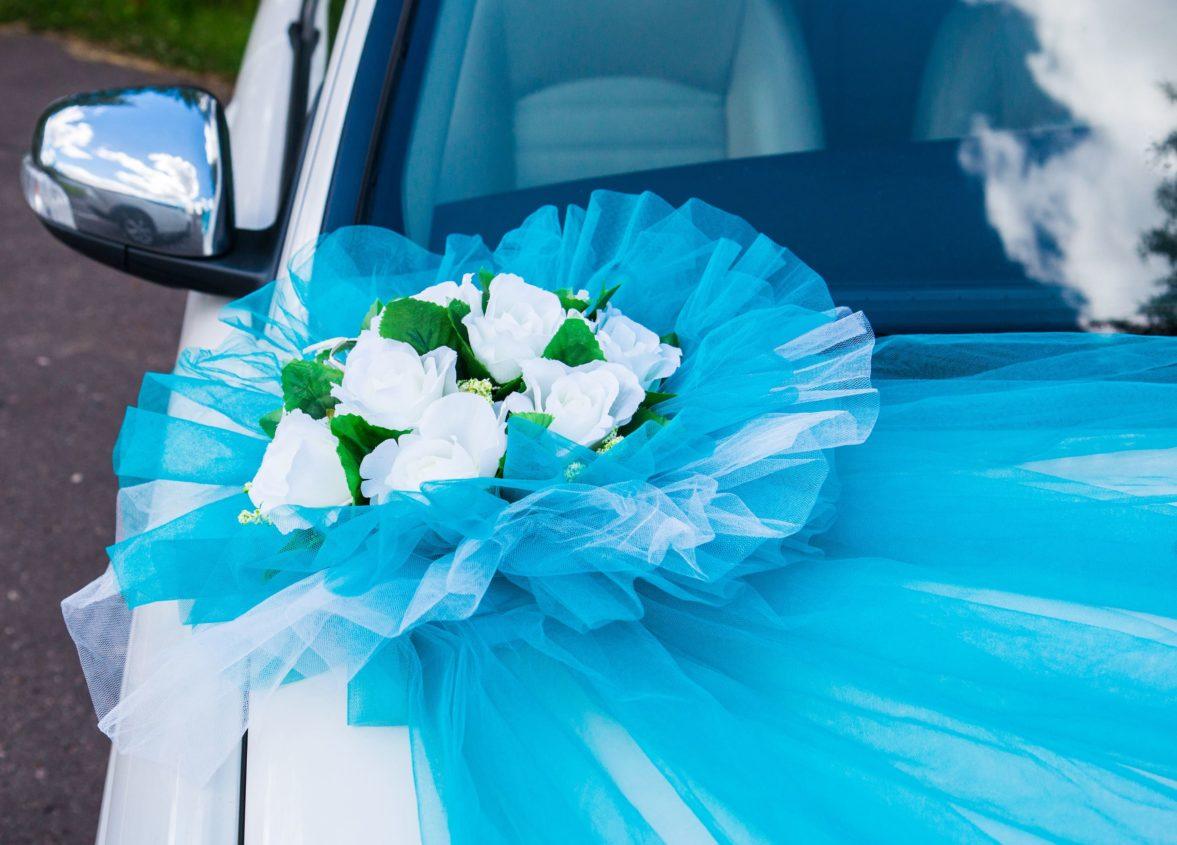Голубое украшение на машину с белыми бутонами цветов в середине.