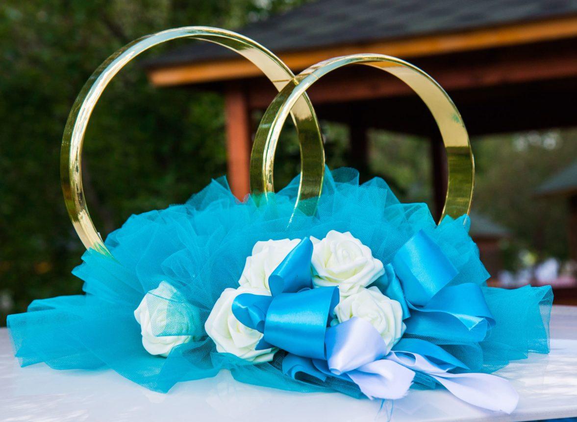 Голубое украшение на машину с атласной отделкой и золотистыми кольцами.