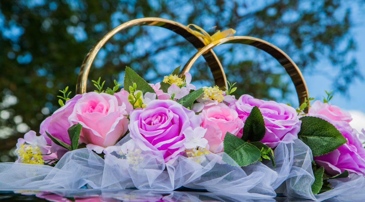 Розово-лиловое украшение на машину с кольцами и нежными бутонами цветов.