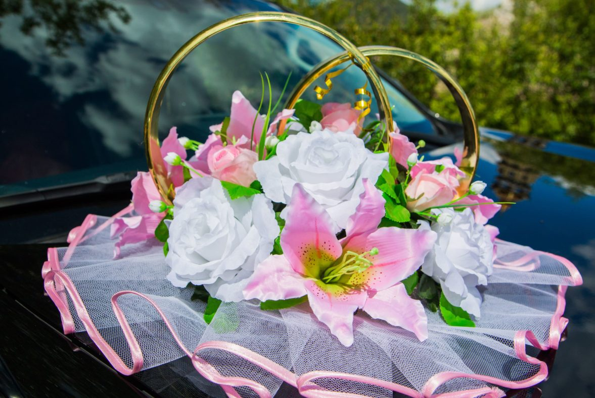 Бело-розовое украшение на машину с бутонами лилий и роз, оформленное оборкой.