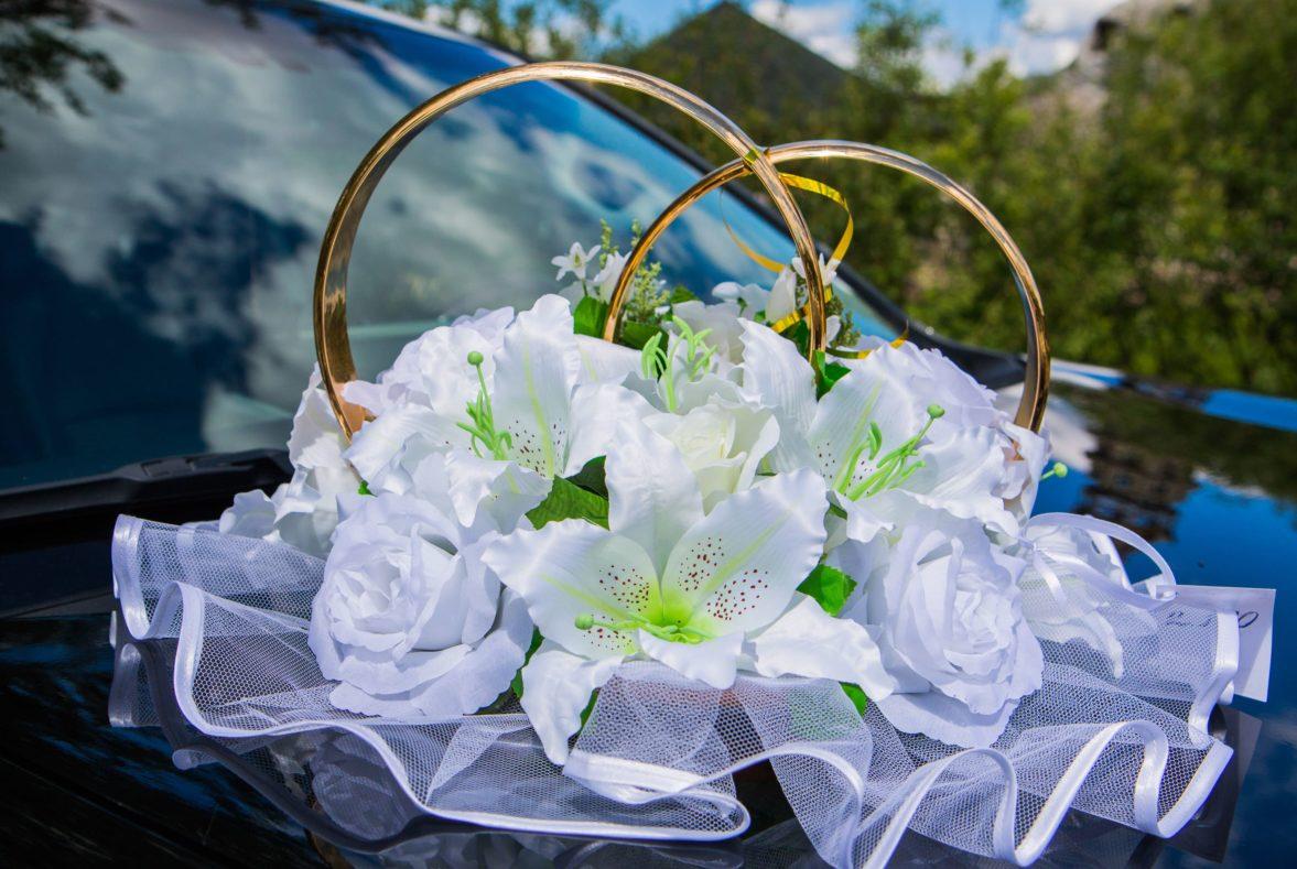 Белое украшение на машину с кольцами и крупными цветочными бутонами.