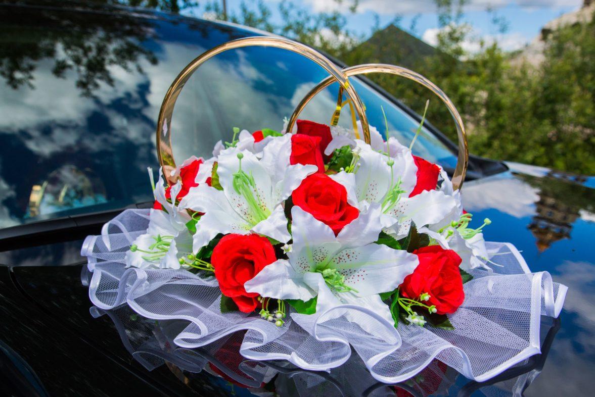 Украшение на машину с выразительными бутонами лилий и роз, а также кольцами.