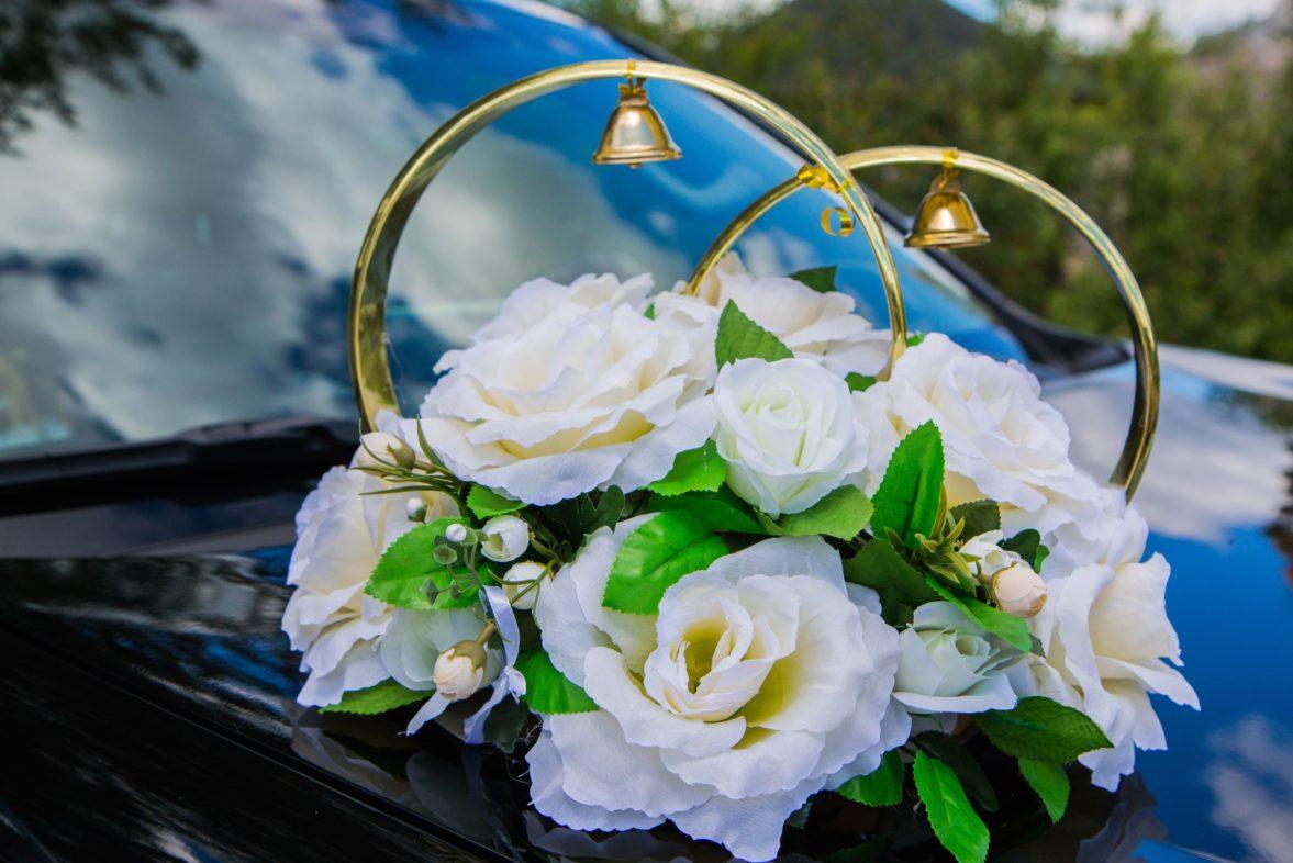 Белое украшение на машину с бутонами и кольцами, украшенными колокольчиками.